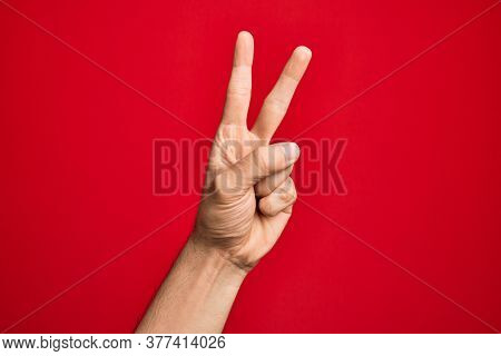 Hand of caucasian young man showing fingers over isolated red background counting number 2 showing two fingers, gesturing victory and winner symbol