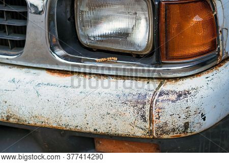 Colse Up To Decay And Rust On The Front Bumper Of An Old White Truck. Rust Hole On Old Worn Painted