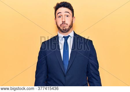 Young hispanic man wearing suit puffing cheeks with funny face. mouth inflated with air, crazy expression.