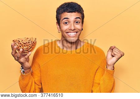 Young african amercian man holding pretzels screaming proud, celebrating victory and success very excited with raised arm