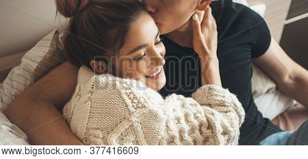 Charming Couple Lying In Bed And Embracing While Kissing And Spending Time Together