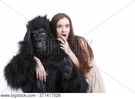 Shocked young woman with irritated man in gorilla costume against white background