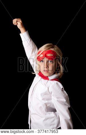 Portrait of young little girl wearing super hero costume in studio