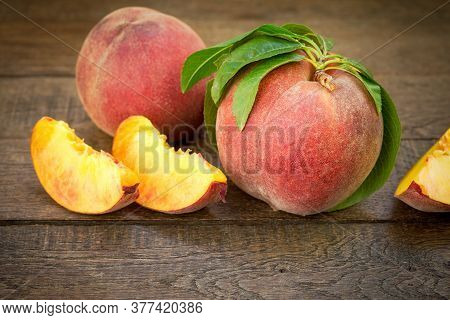 Organic Peach And Slices Of Peach On Rustic Table
