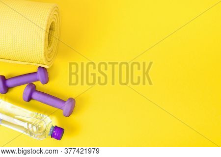 Home Fitness Concept Yellow Yoga Mat, Two Purple Dumbbells And A Bottle Of Water. Equipment For Trai