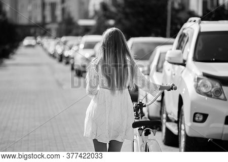 Young Blond Woman In White Dress Walks Away With Bike Near Cars At City, Rear View, Monochrome