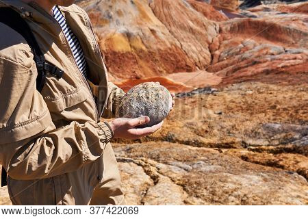 Paleontologist Holding A Dinosaur Fossil Egg In The Background Of A Desert Landscape, Close-up
