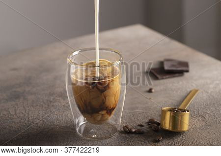 Milk Pouring Into Americano Coffee Glass Cup And Coffee Beans On Concrete Background.