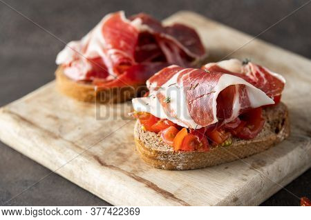 Two Toasts With Fresh Tomatoes And Cured Ham. Delicious Appetiser Italian Prosciutto And Spanish Ibe