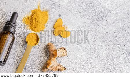 Essential Turmeric Oil In Glass Bottle,  And Turmeric  Roots And Turmeric Powder On Light Concrete B