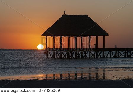 A Hut Over Caribbean Ocean At Sunset, A Little Bird In The Top Of The Hut, Reflections On The Water