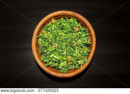 Famous Traditional Arabic Cuisine. Tabbouleh Green Salad In A Brow On Dark Wooden Background. Top Vi