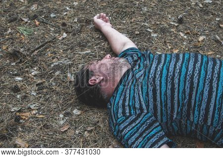 Murder In The Woods. The Body Of A Man In A Blue T-shirt Lies On The Ground Among The Trees In The F