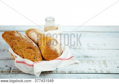 Sourdough Bread And Starter Dough Fresh Baked Bread In Basket With Chocolate Milk Bottle On Wooden T