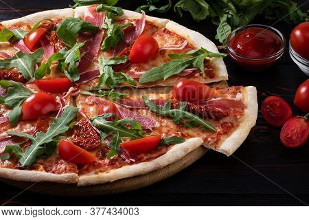 Homemade Pizza With Prosciutto, Sun Dried Tomatoes And Fresh Arugula.