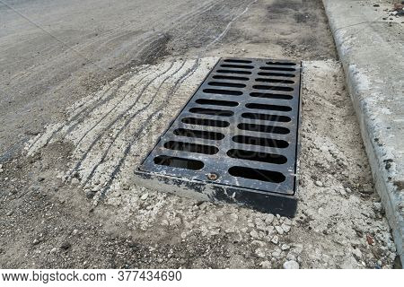 New rainwater grate on the road or sidewalk, installation in concrete. City sewage system for draining water during heavy rain