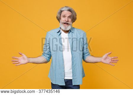Perplexed Worried Elderly Gray-haired Mustache Bearded Man In Casual Blue Shirt Posing Isolated On Y