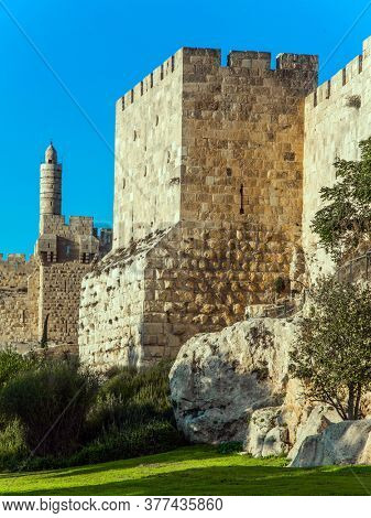 Hot summer sunset. Adorable green lawn growing under ancient walls. The fortress wall of old Jerusalem. Ancient Citadel - Tower of David. The concept of historical, pilgrim and photo tourism