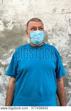 Short-haired Caucasian Ethnicity Mature Man In Blue T-shirt With Medical Mask On His Face To Protect