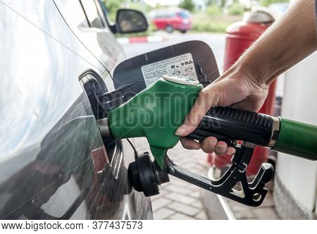 A Young Woman Refuels Her Car At A Gas Station