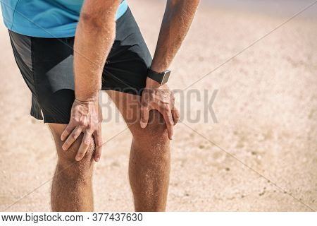 Male runner resting taking a break tired with knee pain after beach jog wearing smartwatch wearable technology for exercise monitoring weight loss.