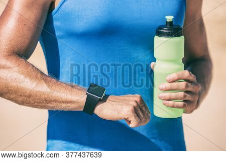 Smartwatch runner man drinking water dehydrated during outdoor run workout training looking at wearable tech smart sports watch.