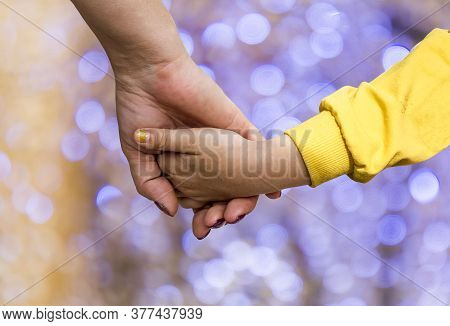 A Woman's Hand Holding The Hand Of A Little Girl Against The Background Of Bokeh