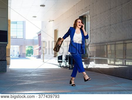 A Funny Businesswoman In A Business Suit Smiles While Talking On The Phone. Business Concept.