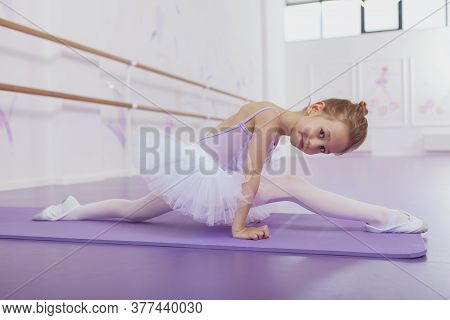 Cute Little Ballerina Girl Exercising At Dance School