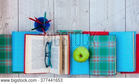 Back To School, Pile Of Books In Colorful Covers And Green Apple On Wooden Table Background. Distanc