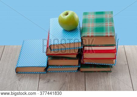 Back To School, Pile Of Books In Colorful Covers And Green Apple On Wooden Table With Blue Backgroun
