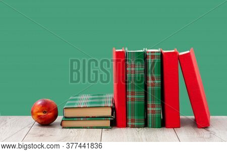 Back To School, Pile Of Books In Colorful Covers And Red Peach On Wooden Table With Green Background