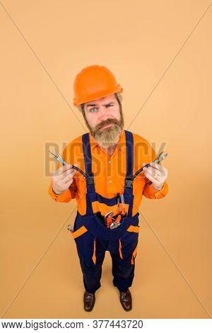Repair. Industry. Builder Man. Serious Worker Holds Repair Tools. Building. Builder In Construction