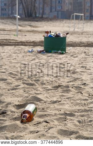 Sandy Beach Littered With Trash And Empty Bottles