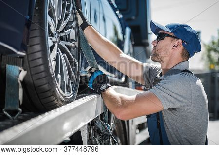 Caucasian Towing Truck Driver In His 40s Securing Transported Modern Blue Vehicle. Transportation An