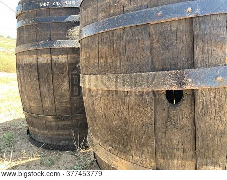 Wooden Oak Barrels With A Metal Rim. Wooden Barrel With A Hole. Wooden Containers For Water And Othe