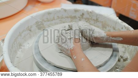 Making ceramic pot on turning pottery wheel