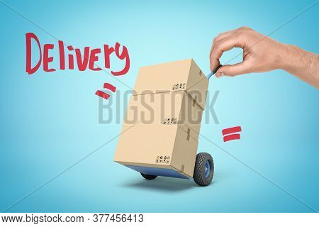 Hand Holding Tiny Hand Truck With Cardboard Boxes And Delivery Sign On Blue Background