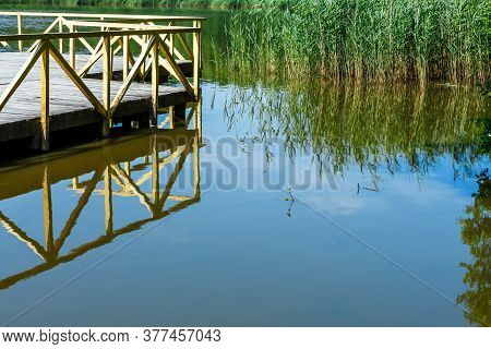 Wooden Flooring With Railings Is Reflected In The Water Of A Small Lake