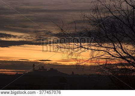A Tree Silhouette In The Foreground And La Seu Vella Cathedral In The Background With An Orange Clou