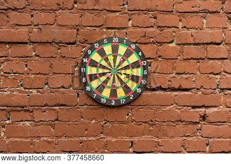 Darts Stuck On Dartboard Mounted On Brick Wall. Darts Hit Target. Dartboard On A Brick Wall.