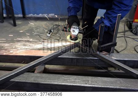 Grinding Metal.grinding Wheel. Locksmith Cleans Iron Corner After Welding In Workshop. Sparks Are Fl