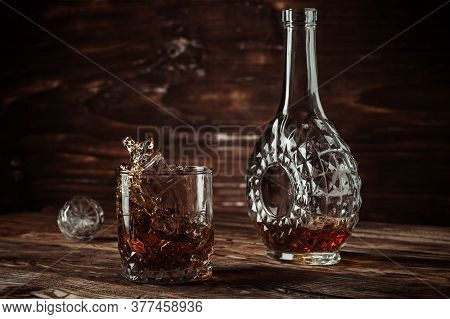 A Bottle Of Whiskey, Cognac Or Brandy And A Glass With A Splash Of The Drink From A Falling Ice Cube