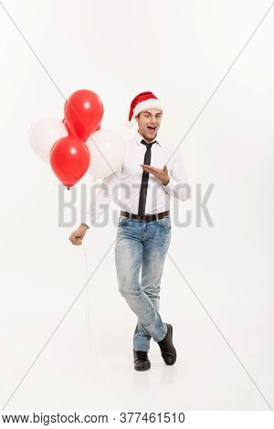 Christmas Concept - Handsome Happy Business Man Wear Santa Hat Giving Red Balloon For Merry Christma
