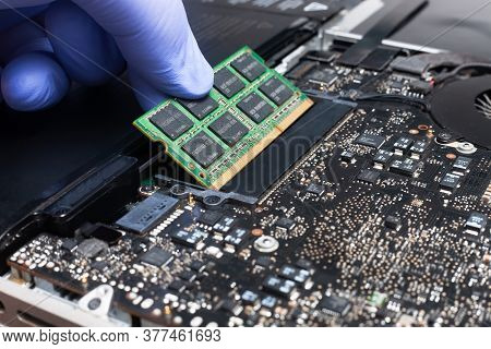 Service Engineer Install New Ram Memory Chips To The Laptop. Repairing And Upgrading Laptop Concept.