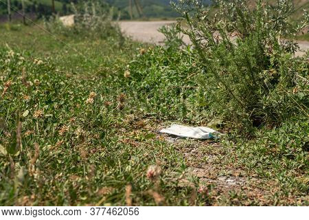 Discarded Used Medical Mask On The Side Of The Road. Human Pollution Of The Environment