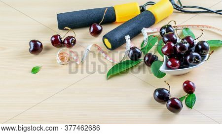 Fresh Cherry Berries, Dosing Tape And Jump Rope On The Wooden Background. Symbols Of Proper Nutritio