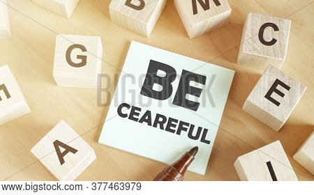 Wooden Cubes With Letters Of The Alphabet, A Piece Of Paper With The Text Be Careful In The Middle O