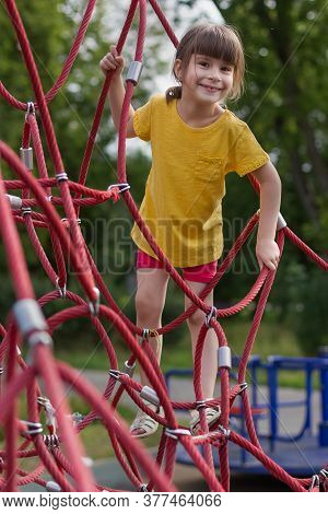 Cute Girl Climbing The Net In The Playground. Free Time In Summer Time