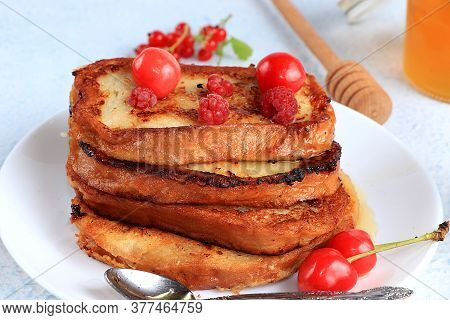 French Toast On A Light Table With Honey, Milk And Berries. Fried Bread With Milk And Scrambled Eggs
